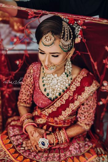 bride wearing contrasting jewellery and maangtikka and jhoomar