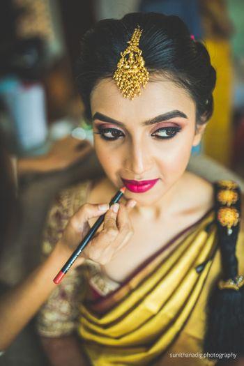 mua putting bright red lipstick on bride