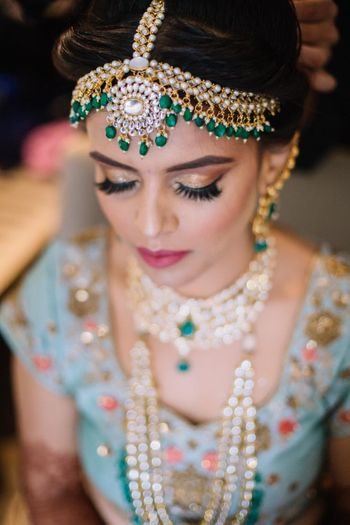 bride with gold eye makeup and green kundan mathapatti