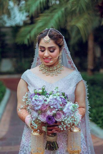 Photo of bride holding bouquet wearing lilac lehenga