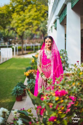 Photo of bright pink fuschia rani pink bridal lehenga with emerald necklace