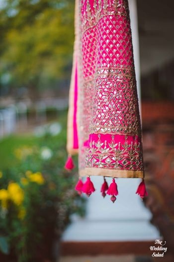 Photo of pink gota patti dupatta with pom poms hung on window