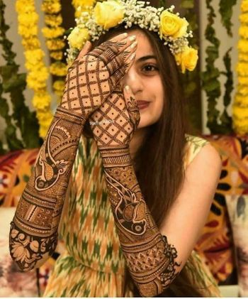 Bride with intricate back hand mehndi design.