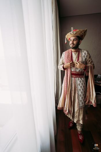 Groom in an off-white embroidered sherwani.