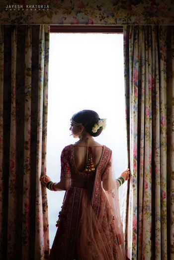 bride near window shot on wedding day