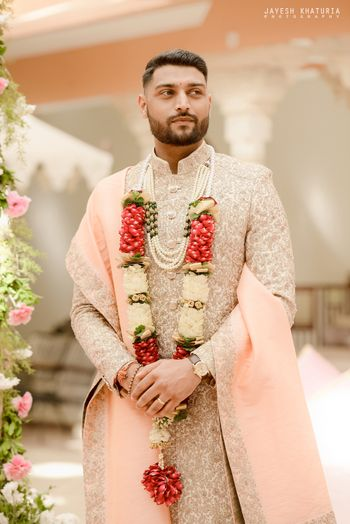 cream and peach sherwani for the groom