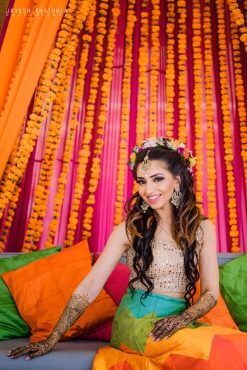 bride on mehendi seat with genda phool decor and floral wreath