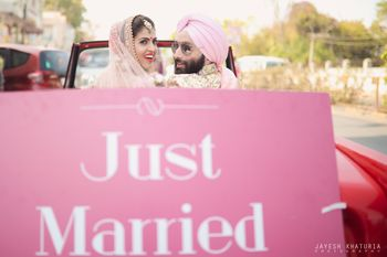couple exit car with just married prop