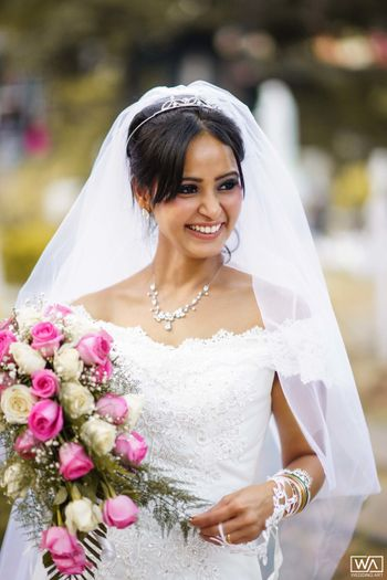A happy bride holding a beautiful bouquet.