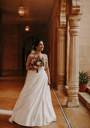 christian bride in white gown and colourful bouquet
