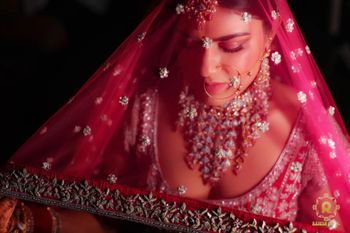 bride holding her red dupatta as veil