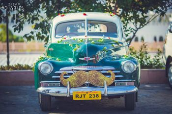 Photo of Groom entry car with sparkly moustache prop