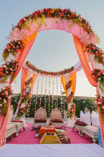 Photo of Light pink and red mandap with flowers
