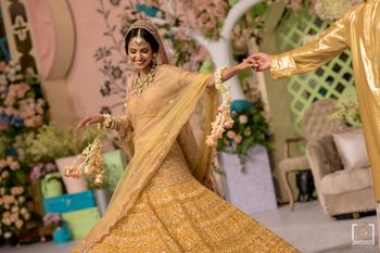 Twirling bride shot of a bride in a bright yellow golden lehenga