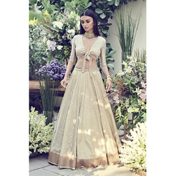 Photo of unique engagement lehenga in beige with tie up blouse