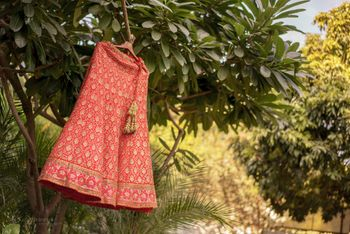 Red and Gold Motifs Lehenga on a Hanger