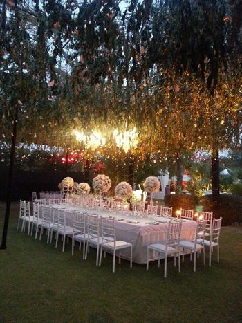 Photo of White Table Decor with Hanging Lights and Floral Decor