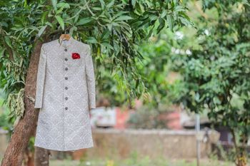 White Sherwani with Red Pocket Square on a Hanger