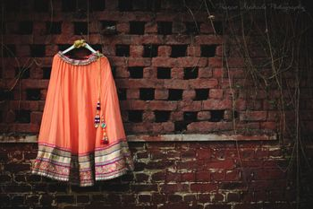 Peach lehenga on hanger in front of rustic wall