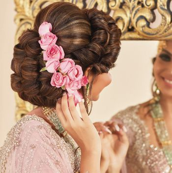 Photo of A stunning bridal bun with pink roses.