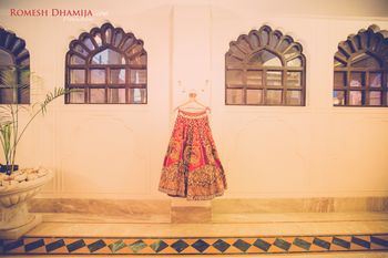 Photo of Orange and Gold Wedding Lehenga on a Hanger
