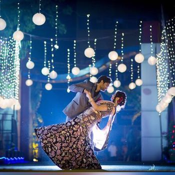 Couple Dancing Under Hanging  Bulbs Shot