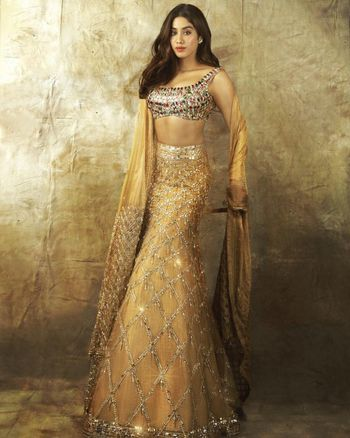 Heavily embellished multistones blouse with golden lehenga.