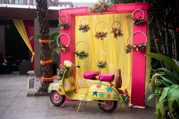 Pink and yellow photobooth decor with a scooter