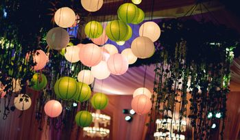 Photo of Hanging lanterns green apply and blush pink for indoor banquet decor