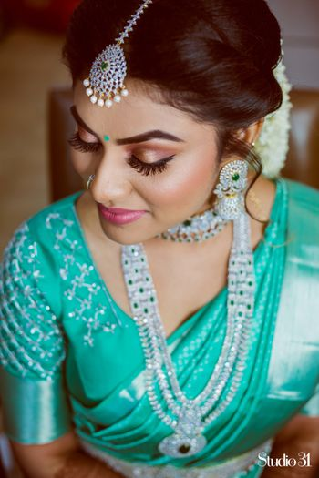 A portrait of a bride dressed in turquoise saree