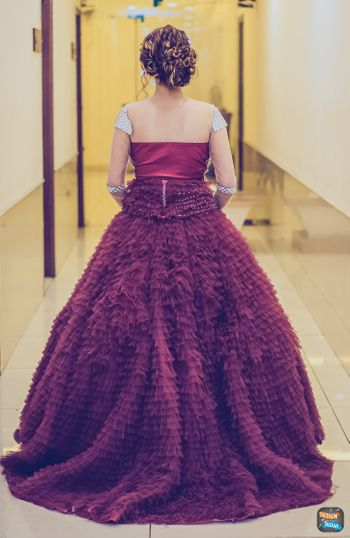 Photo of Deep wine colored ruffled gown on bride