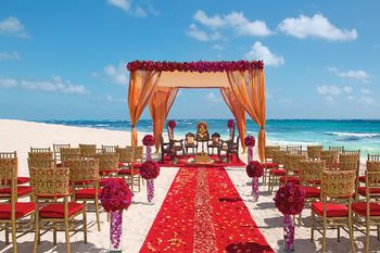 A gorgeous mandap set up by the sea in hues of gold and red