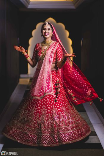 Photo of Red and pink bridal lehenga happy bride