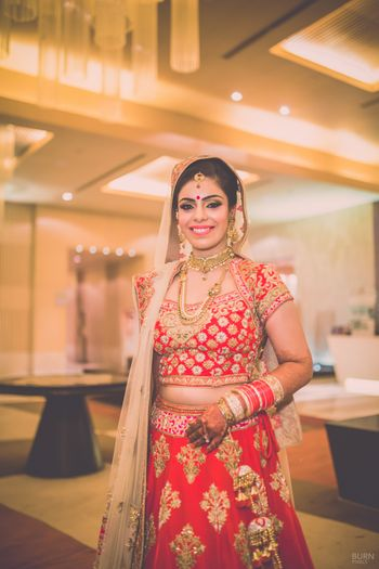 Photo of Smiling Bride in Red and Gold Lehenga