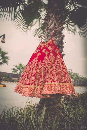 Red and Gold Bridal Lehenga on a Hanger