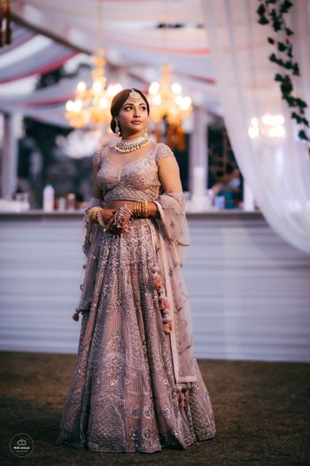 Candid click of a bride wearing a silver lehenga.