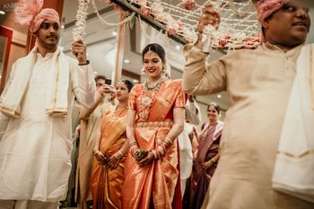A South Indian bride making an entry under a phoolon ki chaadar.