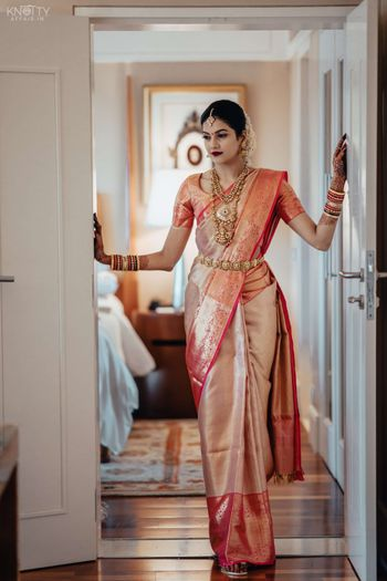 A candid shot of a bride dressed in her wedding saree
