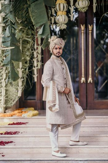 A groom dressed in white and gold sherwani on his wedding day