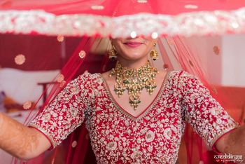 A beautiful veil shot of a bride dressed in red.