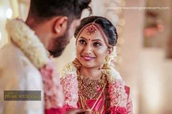Candid shot of a South Indian bride wearing a light pink saree and temple jewellery.