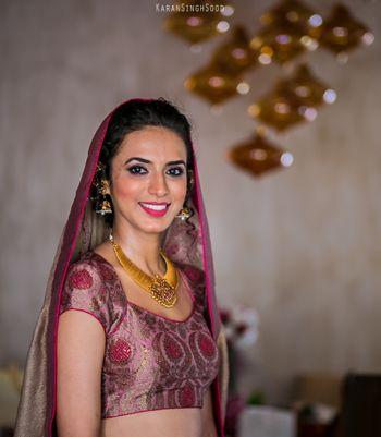Bride wearing Gold Jewelry and Pink Lehenga