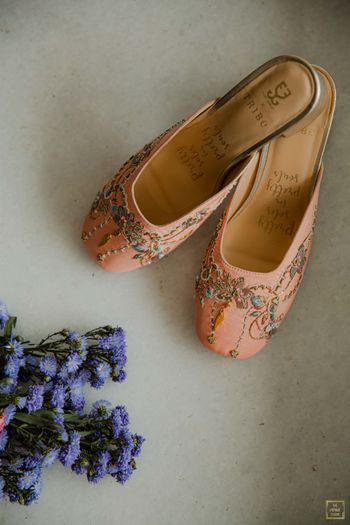 Peach juttis with floral embellishments for the bride