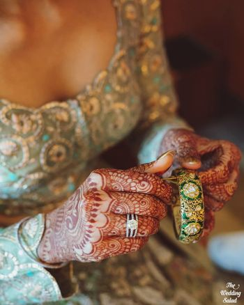 Photo of A stunning getting ready shot of a bride fixing her jewellery.