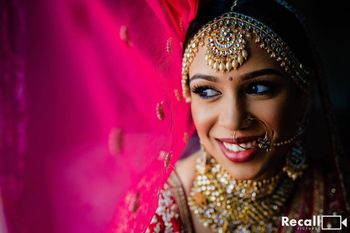 A bride posing with her dupatta on her wedding day.