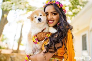 Photo of A bride posing with her dog on her mehndi ceremony