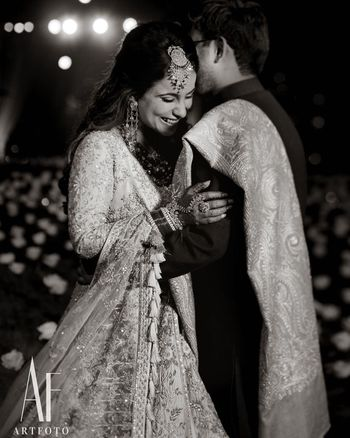 Photo of A candid shot of a bride and groom hugging each other.