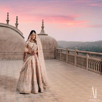 A regal shot of a bride dressed in a pink lehenga.