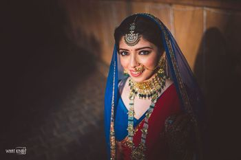 Bride dressed in a blue lehenga with a red dupatta