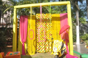 Photo of yellow and pink photo booth with frames